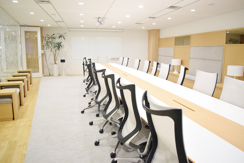 大会議室はミーティングテーブルと椅子だけでなく、両サイドの壁際にも椅子が置かれて大人数の会議に対応している