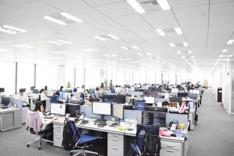 窓に囲まれて開放感のある執務スペース。経営層のデスクも同じ空間に置かれ、社内の風通しの良さが感じられる