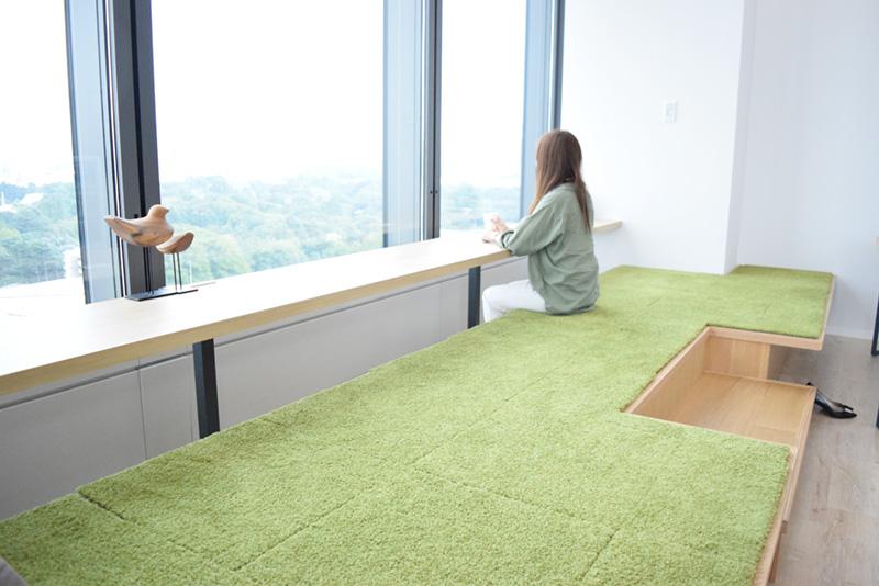 わいわいゾーンにあるリラックススペースには芝生風のカウンター。新宿御苑を見下ろす癒しの空間となっている