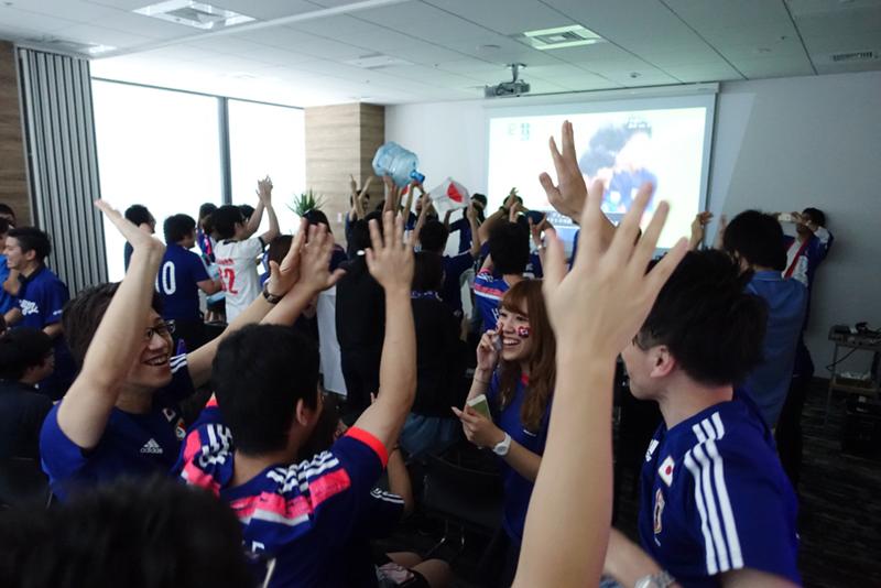 オフィスに集まってサッカー観戦する社員たち